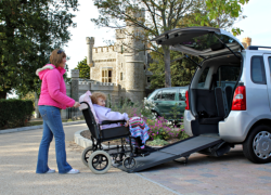 daughter assisting her mother into the back of a wheelchair access vehicle